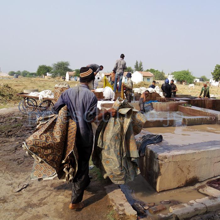 乾いたアジュラックの布を洗い場に運ぶ