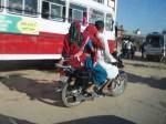 インド、原色のサリーをまといバイクに乗るラジャスタン女性
